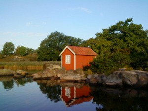 En röd liten stuga på Tjärö i tidigt morgonljus
